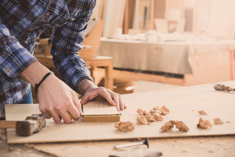 Ξυλουργός που κρατά μια ταινία μέτρου στον πίνακα Πάγκος εργασίας ξυλουργικής στοκ φωτογραφία