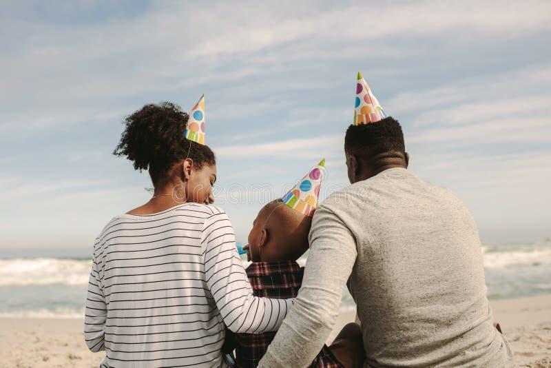 Οικογένεια με τα καπέλα κομμάτων που φυσούν το συριγμό στην παραλία στοκ φωτογραφία