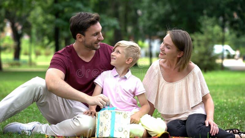 Οικογένεια που δίνει το αιφνιδιαστικό δώρο στον μπαμπά στην ημέρα πατέρων ή που γιορτάζει τα γενέθλιά του στοκ εικόνες