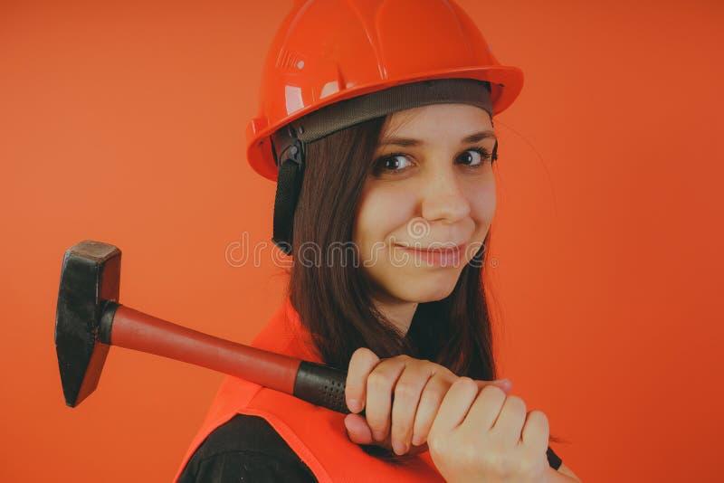 Οικοδόμος κοριτσιών με το σφυρί διαθέσιμο, έννοια: κορίτσι που κάνει τις επισκευές στοκ εικόνες