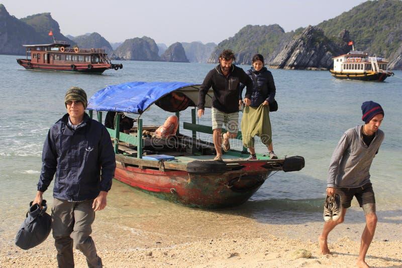 Οι άνθρωποι αφήνουν το σκάφος στην ακτή στοκ εικόνες
