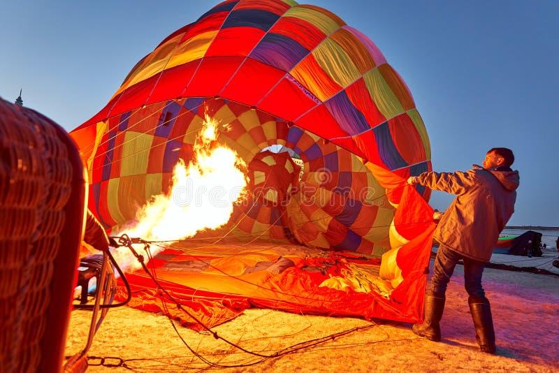 Οι άνθρωποι διογκώνουν ένα τεράστιο μπαλόνι με ένα καλάθι με έναν καυστήρα αερίου στοκ εικόνα με δικαίωμα ελεύθερης χρήσης