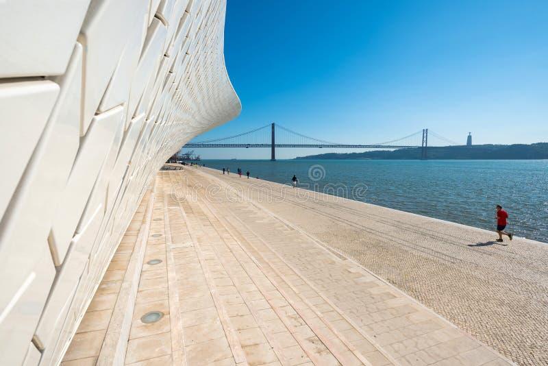 Οι άνθρωποι περπατούν κοντά στο διάσημο μουσείο MAAT στη Λισσαβώνα κοντά στον ποταμό Tagus και το ορόσημο 25 της γέφυρας Απριλίου στοκ φωτογραφίες