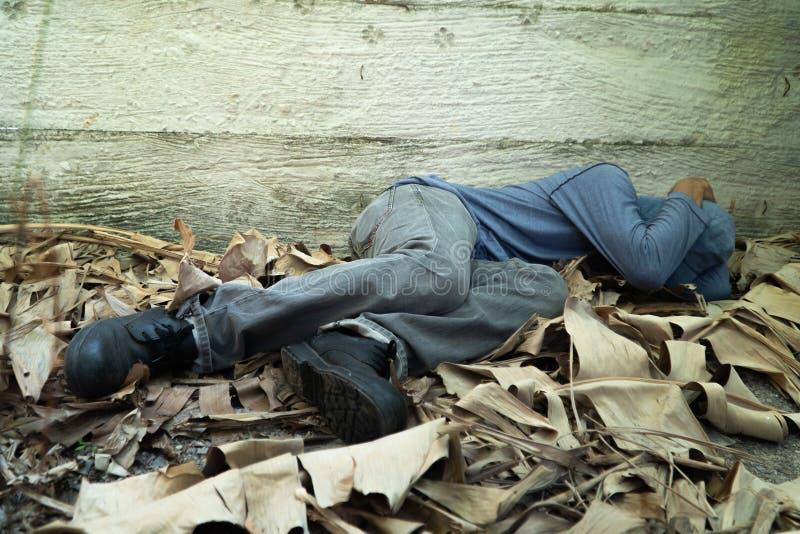Οι άστεγοι φόρεσαν ένα γκρίζο καπέλο και ένα γκρίζο πουκάμισο μακρύς-μανικιών Κοιμάται λόγω της εξαγωγής, με την πίσω κλίση ενάντ στοκ εικόνες με δικαίωμα ελεύθερης χρήσης