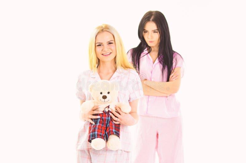 Οι αδελφές στις πυτζάμες φαίνονται μη φιλικές, ζηλότυπος Κορίτσια στις ρόδινες πυτζάμες, απομονωμένο άσπρο υπόβαθρο Κυρία ζηλότυπ στοκ φωτογραφία