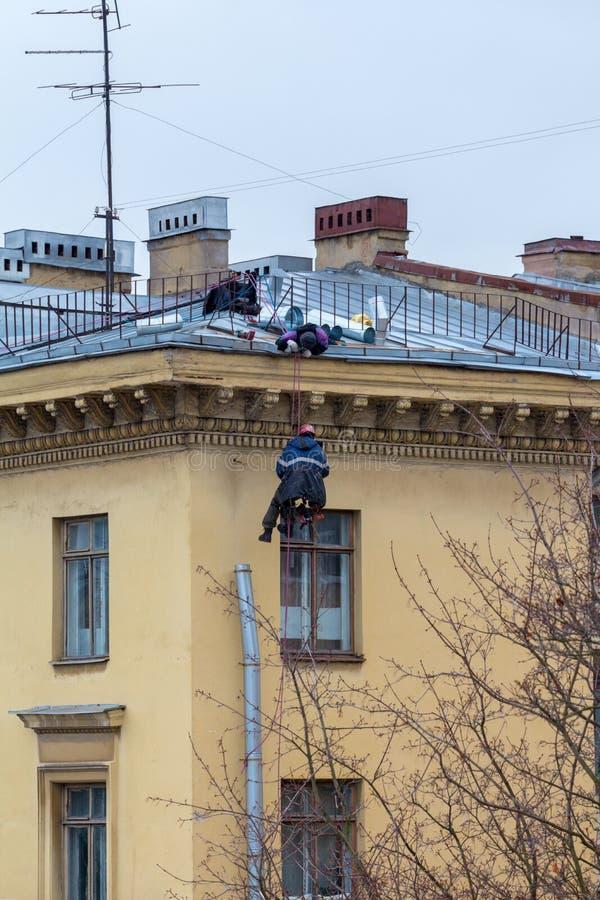 Οι βιομηχανικοί ορειβάτες επισκευάζουν έναν σωλήνα αποχέτευσης στον τοίχο ενός κατοικημένου κτηρίου στοκ εικόνα με δικαίωμα ελεύθερης χρήσης