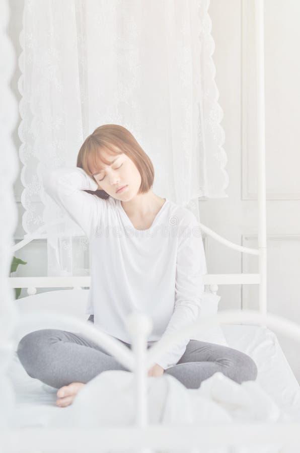 Οι γυναίκες κάθονται στην άκρη του κρεβατιού στοκ εικόνες