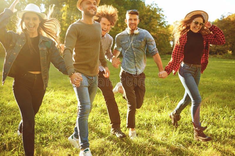 Οι εύθυμοι φίλοι τρέχουν στο πάρκο στοκ εικόνα