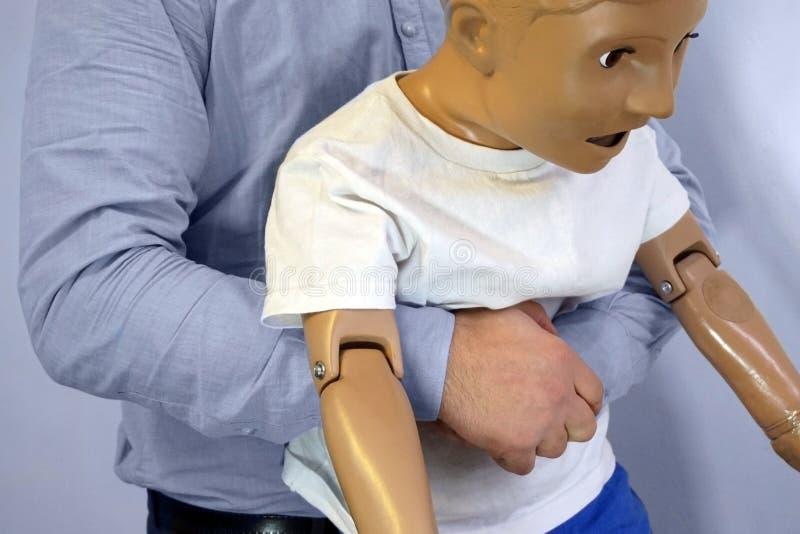 Οι κοιλιακές ωθήσεις ο ελιγμός Heimlich ή το Heimlich ελίσσονται σε ένα ομοίωμα παιδιών μανεκέν προσομοίωσης κατά τη διάρκεια της στοκ εικόνες