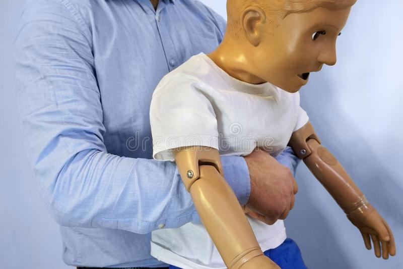 Οι κοιλιακές ωθήσεις ο ελιγμός Heimlich ή το Heimlich ελίσσονται σε ένα ομοίωμα παιδιών μανεκέν προσομοίωσης κατά τη διάρκεια της στοκ εικόνα