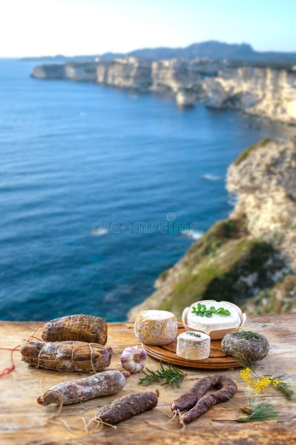 Οι κορσικανικές άγριες λιχουδιές χοιρινού κρέατος, και το τυρί έκαναν στην Κορσική με το υπόβαθρο πανοράματος απότομων βράχων κόλ στοκ εικόνες