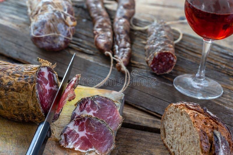 Οι κορσικανικές άγριες λιχουδιές χοιρινού κρέατος, και το τυρί έκαναν στην Κορσική Γαλλία στο ξύλινο υπόβαθρο με το ποτήρι του κό στοκ εικόνα