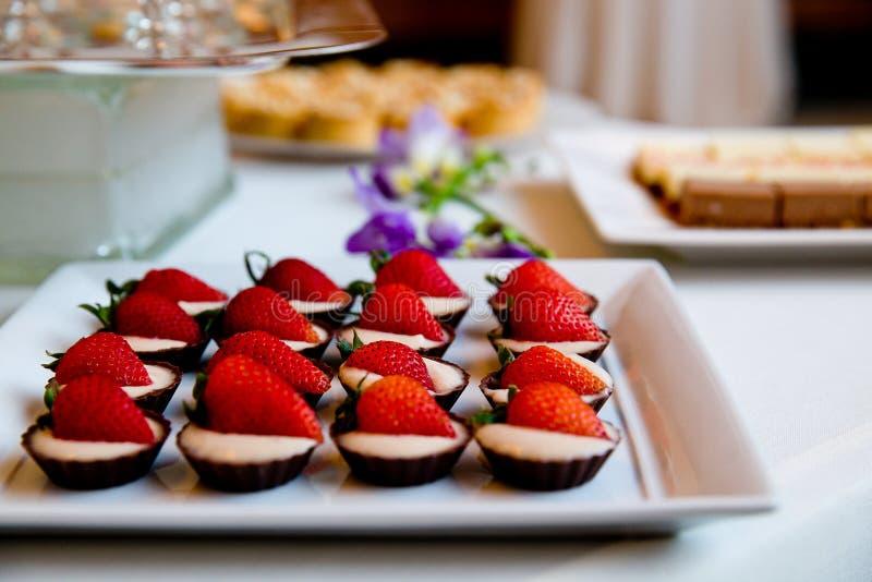Οι λεπτομέρειες του γάμου μεταχειρίζονται με την άσπρες κρέμα και τις φράουλες στα φλυτζάνια σοκολάτας στοκ φωτογραφίες