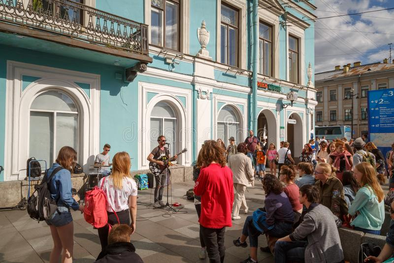 Οι μουσικοί τραγουδούν τα τραγούδια στην οδό μπροστά από ένα πλήθος των περαστικών και των τουριστών στην ημέρα άνοιξη ήλιων στοκ εικόνα