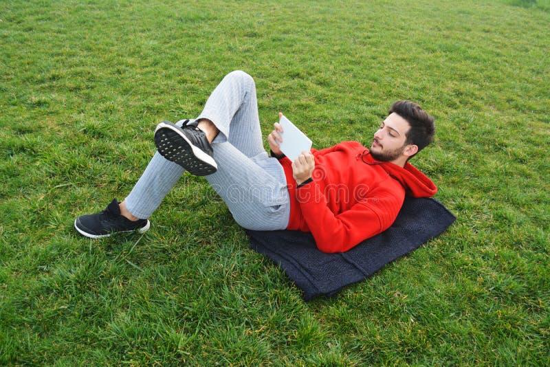 Οι νεαροί άνδρες που χρησιμοποιούν την ψηφιακή ταμπλέτα σταθμεύουν δημόσια στοκ φωτογραφίες με δικαίωμα ελεύθερης χρήσης