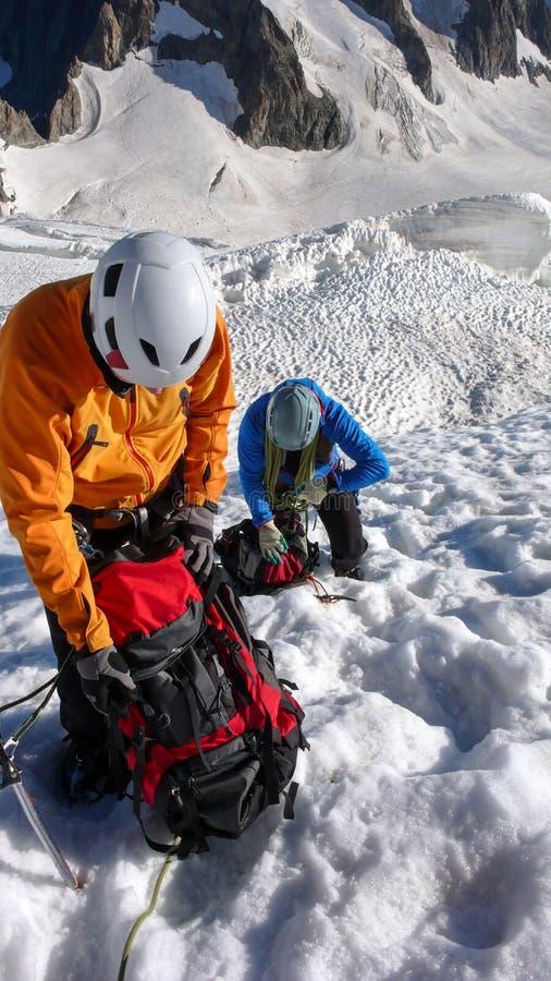 Οι ορειβάτες βουνών παίρνουν ένα σπάσιμο υψηλό επάνω σε έναν παγετώνα στις γαλλικές Άλπεις στοκ εικόνα με δικαίωμα ελεύθερης χρήσης
