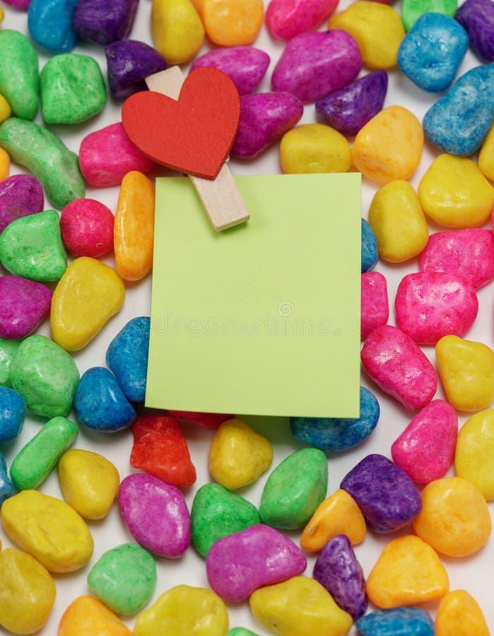 Οι σημειώσεις Πράσινης Βίβλου στερέωσαν με ένα ξύλινο clothespin με μορφή καρδιών στο υπόβαθρο από το χρωματισμό των πετρών στοκ εικόνες