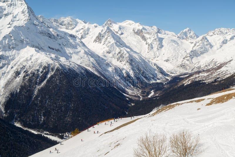 Οι σκιέρ και τα snowboarders οδηγούν στις χιονώδεις κλίσεις στα πλαίσια των αιχμών των βουνών Καύκασου στοκ εικόνα