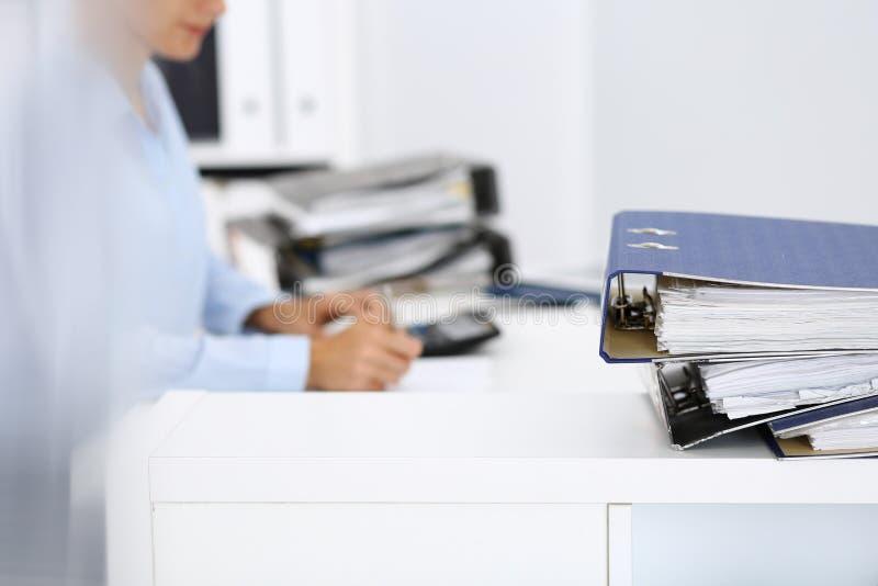 Οι σύνδεσμοι με τα έγγραφα περιμένουν να υποβληθούν σε επεξεργασία από την επιχειρησιακό γυναίκα ή το λογιστή πίσω στη θαμπάδα Εσ στοκ φωτογραφία με δικαίωμα ελεύθερης χρήσης