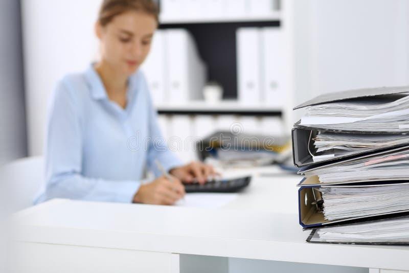 Οι σύνδεσμοι με τα έγγραφα περιμένουν να υποβληθούν σε επεξεργασία από την επιχειρησιακό γυναίκα ή το λογιστή πίσω στη θαμπάδα Εσ στοκ φωτογραφία