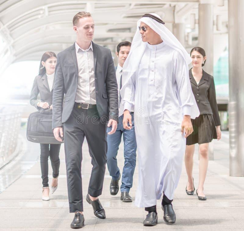 Οι σφαιρικοί επιχειρησιακοί αραβικοί και διεθνείς επιχειρηματίες περπατούν και μιλούν τις επιχειρησιακές διαπραγματεύσεις και το  στοκ φωτογραφία