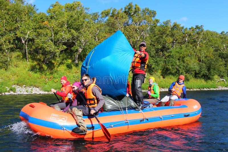 Οι τουρίστες επιπλέουν στον ποταμό με μια μπλε σκηνή υπό μορφή πανιού στοκ εικόνες