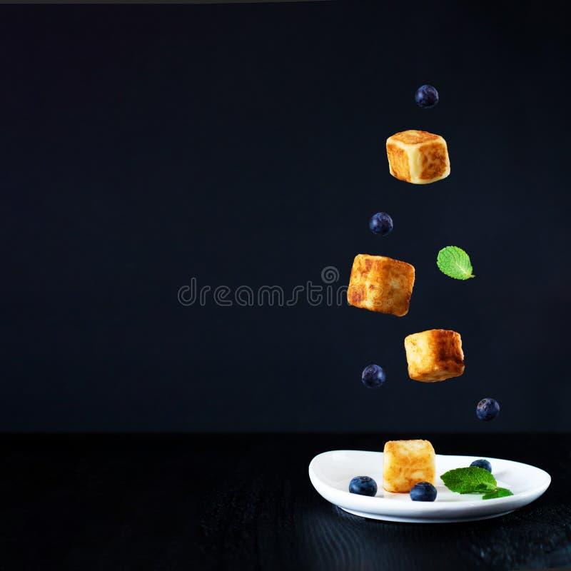 Οι τρεις κύβοι τυριών εξοχικών σπιτιών, βακκίνια και φύλλα μεντών που πέφτουν κάτω από ένα είναι στο άσπρο πιάτο, στο μαύρο υπόβα στοκ εικόνες