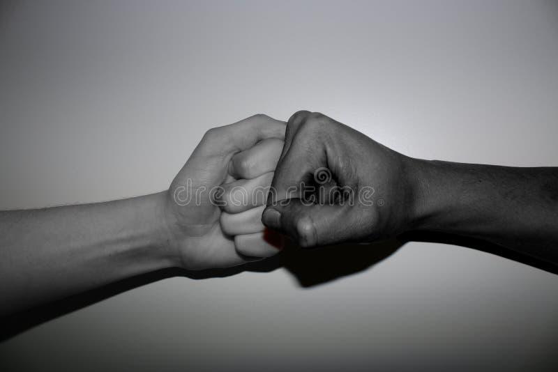 Οι χειρονομίες χεριών - πρόσκρουση πυγμών του differenend δύο - πολυ που χρωματίζεται παραδίδουν γραπτό στοκ εικόνες
