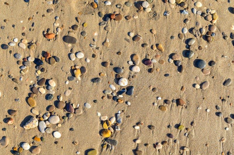 Οι πολύχρωμες μικρές πέτρες που βρίσκονται στο επίπεδο ακτών άμμου βρέθηκαν στοκ εικόνα