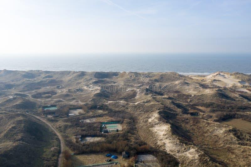 Ολλανδικοί αμμόλοφοι με τη θάλασσα στην πλάτη μια ηλιόλουστη αλλά misty ημέρα στοκ φωτογραφία