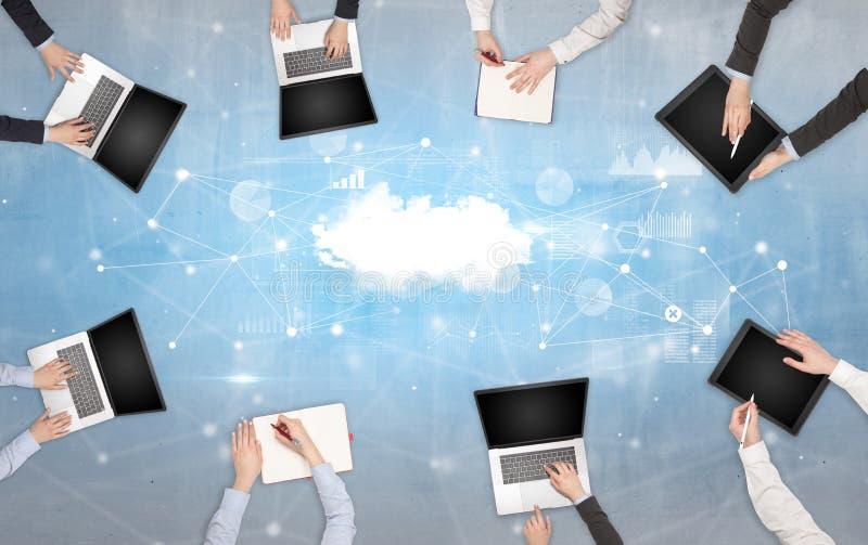 Ομάδα ανθρώπων με τις συσκευές στα χέρια που λειτουργούν στα lap-top και τις ταμπλέτες με τη σε απευθείας σύνδεση έννοια ομαδικής στοκ φωτογραφία με δικαίωμα ελεύθερης χρήσης