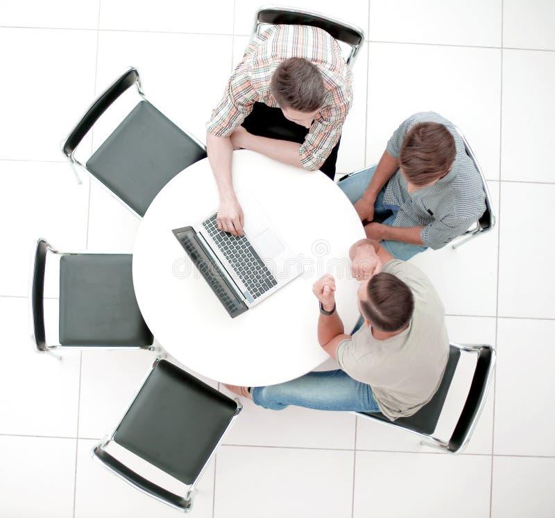 Ομάδα ανθρώπων με τις συσκευές που κάθεται σε μια διάσκεψη στρογγυλής τραπέζης στοκ εικόνες