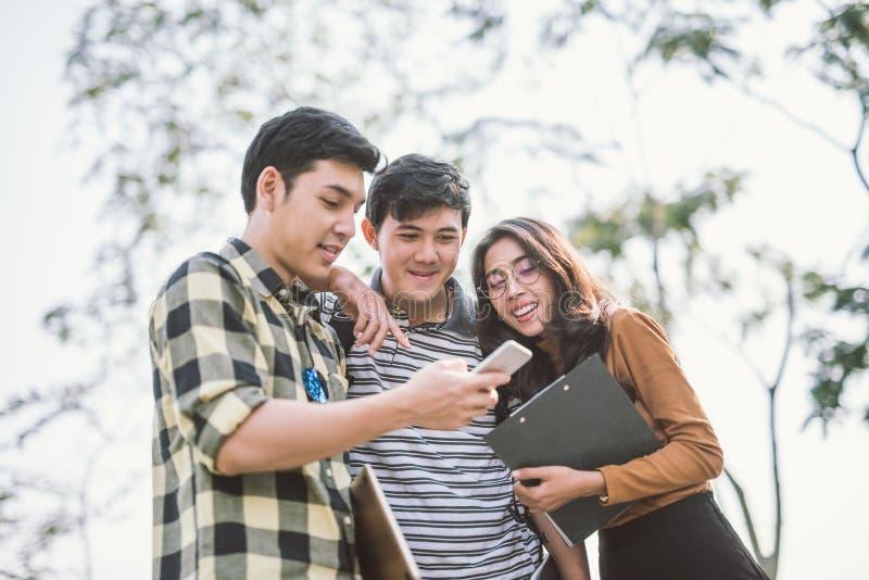 Ομάδα εύθυμων φίλων που προσέχουν το έξυπνο τηλέφωνο υπαίθριο στοκ φωτογραφία με δικαίωμα ελεύθερης χρήσης