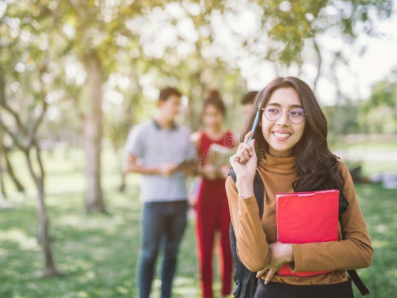 Ομάδα ευτυχών ασιατικών εφηβικών σπουδαστών με τους σχολικούς φακέλλους στοκ φωτογραφίες