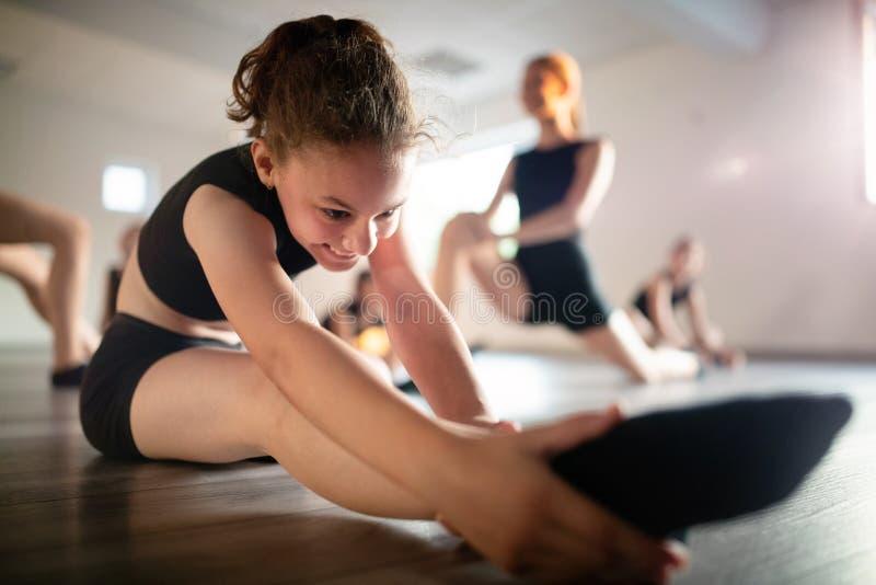 Ομάδα νέων κοριτσιών που ασκούν και που ασκούν το σύγχρονο χορό μπαλέτου στοκ εικόνα