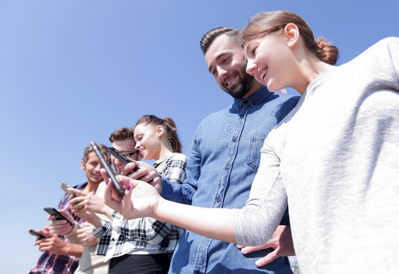 Ομάδα νέων με τις σύγχρονες συσκευές στοκ εικόνες