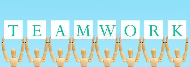 Ομάδα ξύλινου αριθμού που στέκεται και που κρατά την ετικέτα κειμένων στην ομαδική εργασία λέξεων στοκ φωτογραφίες με δικαίωμα ελεύθερης χρήσης