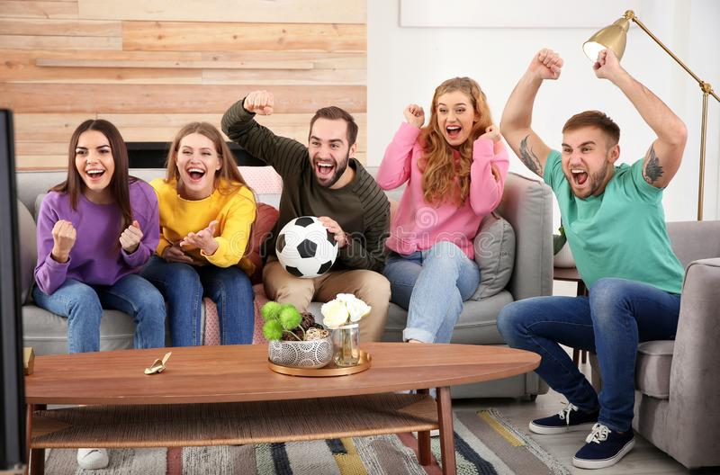 Ομάδα φίλων που γιορτάζουν τη νίκη της αγαπημένης ομάδας ποδοσφαίρου στο δωμάτιο στοκ φωτογραφία
