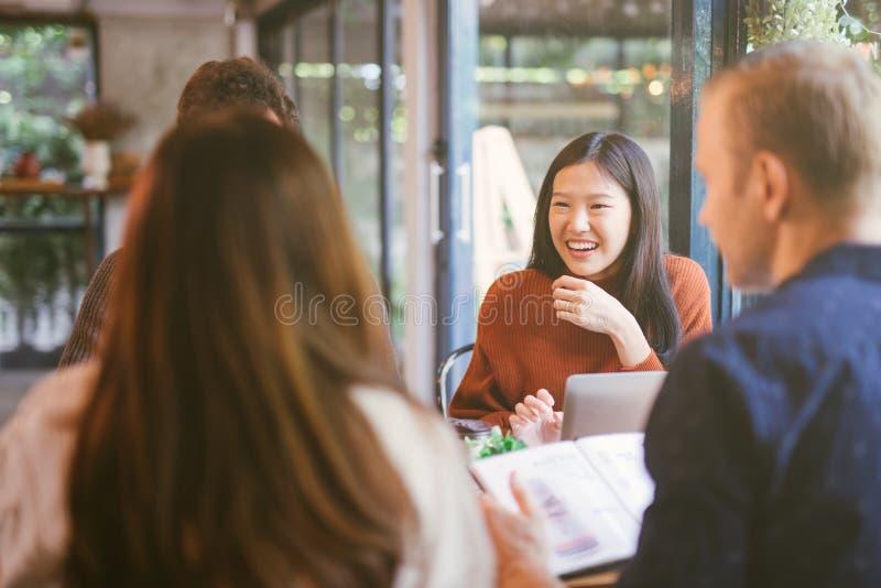 Ομάδα φίλων που κουβεντιάζουν και που χρησιμοποιούν το lap-top στον καφέ στον καφέ καφετεριών στο πανεπιστήμιο που μιλά και που γ στοκ φωτογραφίες