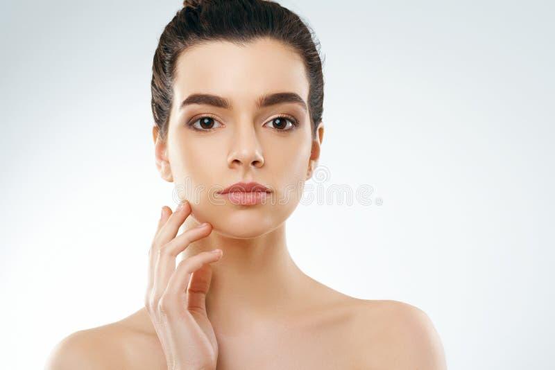 Ομορφιά και έννοια SPA Όμορφη νέα γυναίκα με το καθαρό φρέσκο πρόσωπο αφής δερμάτων Του προσώπου επεξεργασία στοκ εικόνες