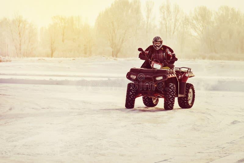 Οδήγηση οδηγών ποδηλάτων τετραγώνων πέρα από μια παγωμένη λίμνη στοκ φωτογραφίες