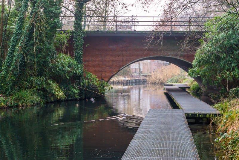 Οδογέφυρα με μια αποβάθρα στο νερό, όμορφο τοπίο ποταμών, το πάρκο του Χίλβερσουμ, οι Κάτω Χώρες στοκ εικόνες με δικαίωμα ελεύθερης χρήσης