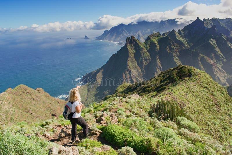 Οδοιπόρος γυναικών που προσέχει το όμορφο πλευρικό τοπίο - Tenerife, Κανάρια νησιά, Ισπανία Δυτική άποψη ακτών, βουνό Anaga στοκ εικόνα με δικαίωμα ελεύθερης χρήσης