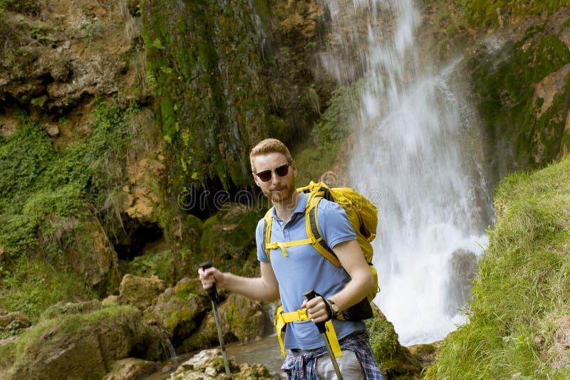 Οδοιπόρος που σταματούν νέος εκτός από έναν καταρράκτη βουνών για να στηριχτεί στοκ εικόνα