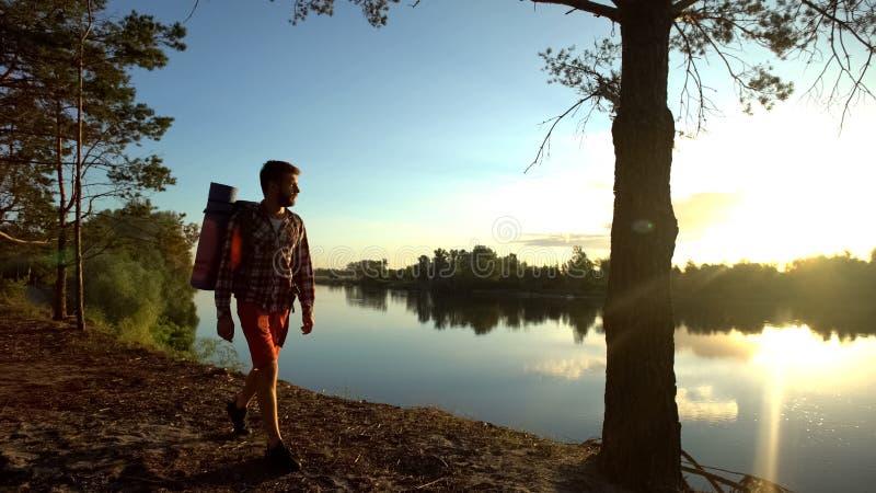 Οδοιπόρος που περπατά κατά μήκος της όχθης ποταμού στη θαυμάσια θέση, που απολαμβάνει την όμορφη θέα στοκ εικόνες