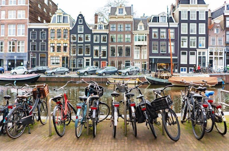 Οδός στο Άμστερνταμ, γιοτ στο κανάλι και χώρος στάθμευσης ποδηλάτων στο πρώτο πλάνο στοκ εικόνες