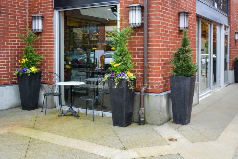 Οδός caffe για δύο στην προθήκη Μαρμάρινος πίνακας, και δύο καρέκλες ως μικρό υπαίθριο καφέ στοκ εικόνες