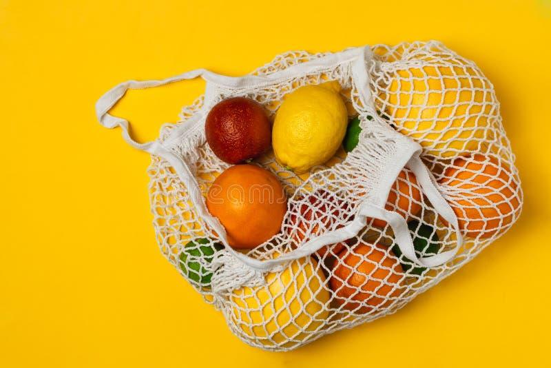 Οργανική ποικιλία εσπεριδοειδών στην επαναχρησιμοποιήσιμη τσάντα αγορών πλέγματος βαμβακιού - ανακύκλωση, βιώσιμος τρόπος ζωής, μ στοκ φωτογραφίες