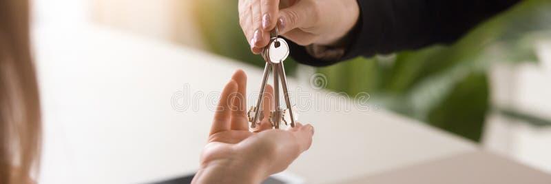 Οριζόντια στενά επάνω αρσενικά χέρια εικόνας που δίνουν τα κλειδιά στο θηλυκό στοκ φωτογραφία