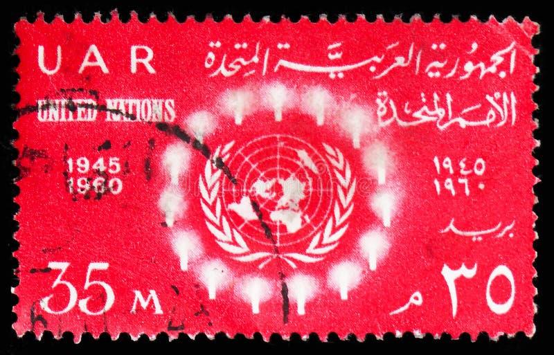 15ος ΟΗΕ επετείου - τα ελαφριά να περιβάλουν Η.Ε συμβολίζουν, οργάνωση Ηνωμένων Εθνών serie, circa το 1960 στοκ φωτογραφία